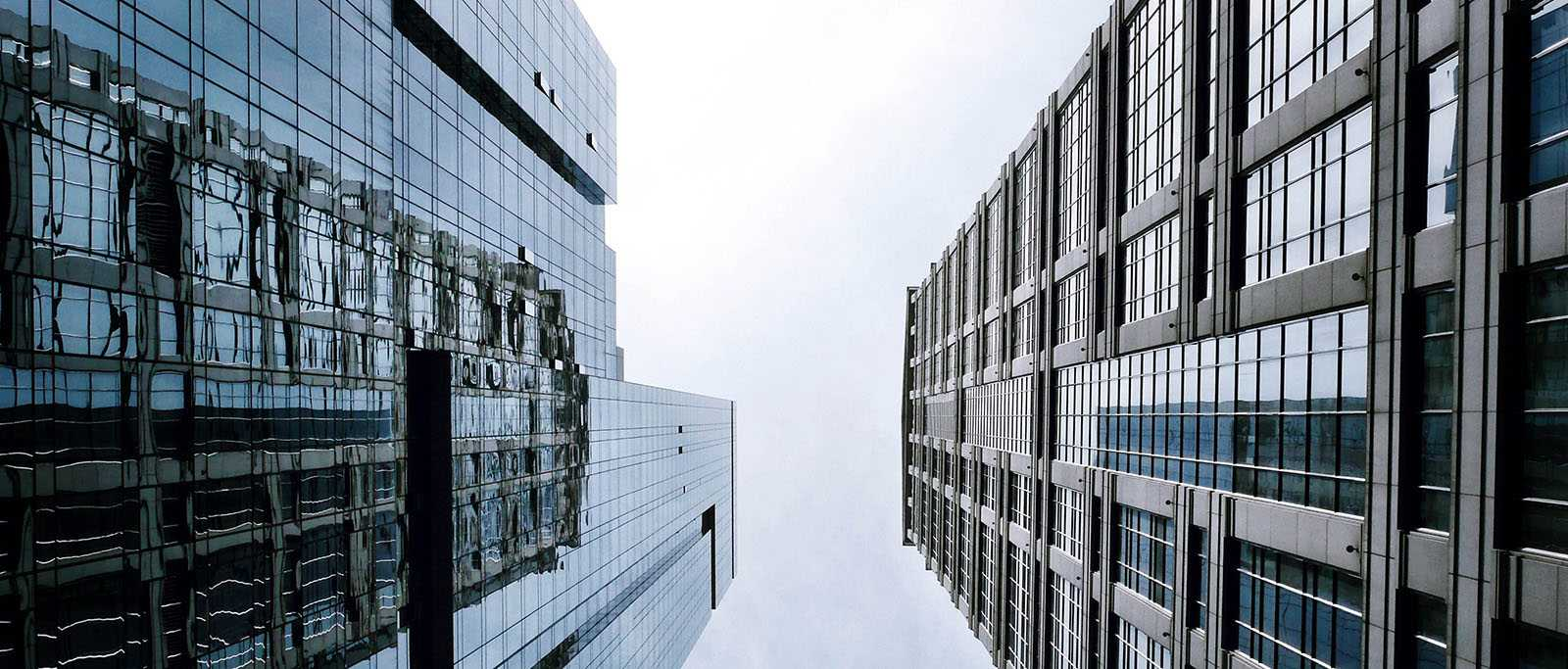 A view looking up at two large skycrapers with cloudy patch of sky between them